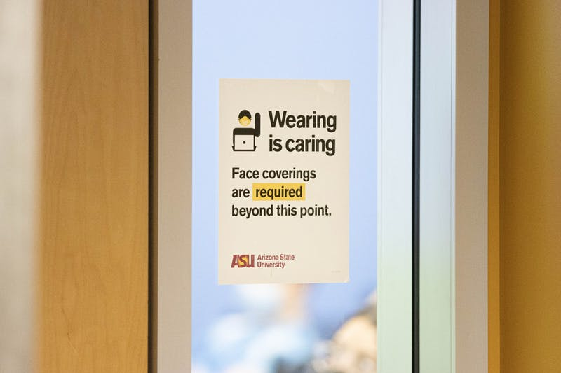 """An ASU sign that says """"wearing is caring, face coverings are now required beyond this point,"""" encouraging mask wearing."""