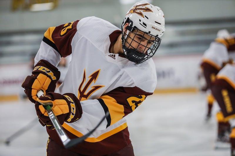 Demetrios Koumontzis (23) raises his stick during an Ice Hockey game