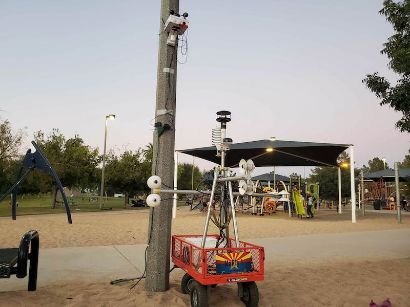 One of the devices is in a red cart in the middle of a park. It sits next to a light pole.
