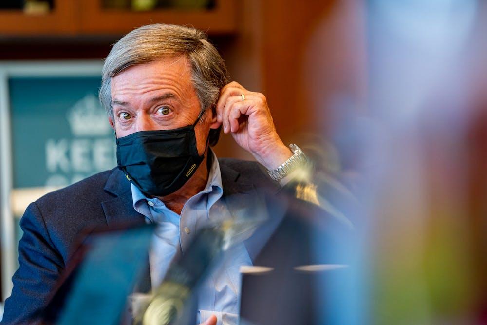 ASU President Michael Crow adjusts his mask