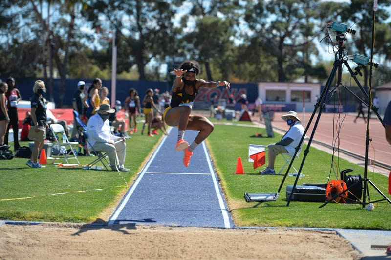 Amanda Carty prepares to land in the sand after the women's triple jump.