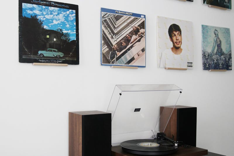 A vinyl record collection mounted on a wall with a record player underneath.