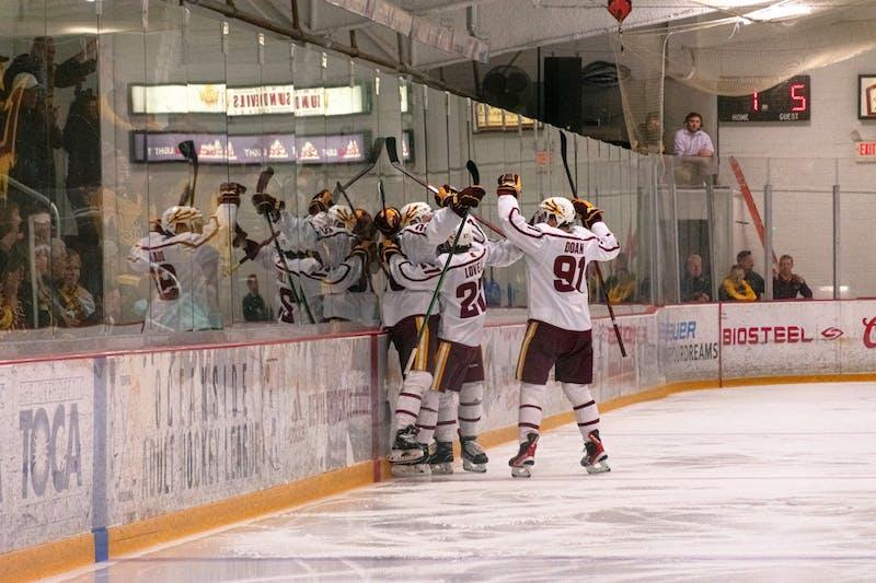 The ASU ice hockey team celebrate a goal against the glass