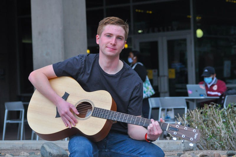 Andrew Kurland posing with his guitar outside the Walter Cronkite Building at ASU.