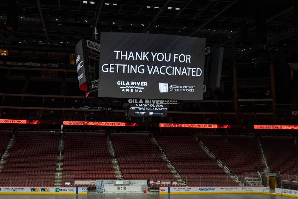 """The center display board at the Gila River Arena vaccine site in Glendale displays a message that says """"Thank you for getting vaccinated"""""""