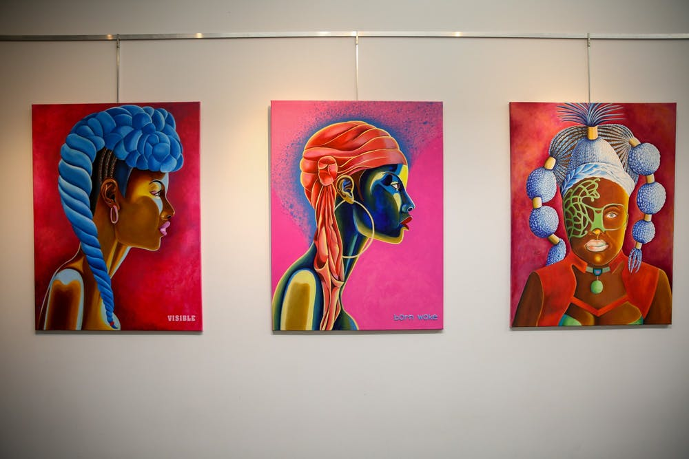 """Two side profile and one portrait painting of the """"This and That"""" art exhibit are shown"""