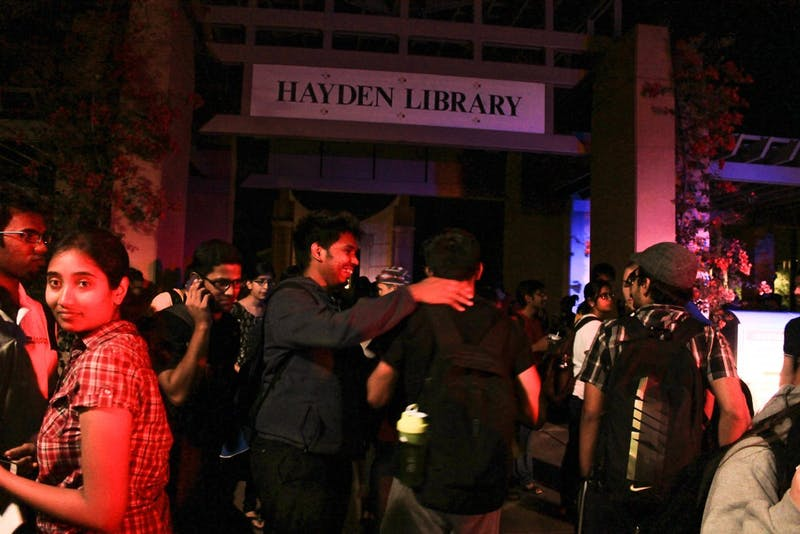 Students gather outside Hayden Library after a fire alarm went o