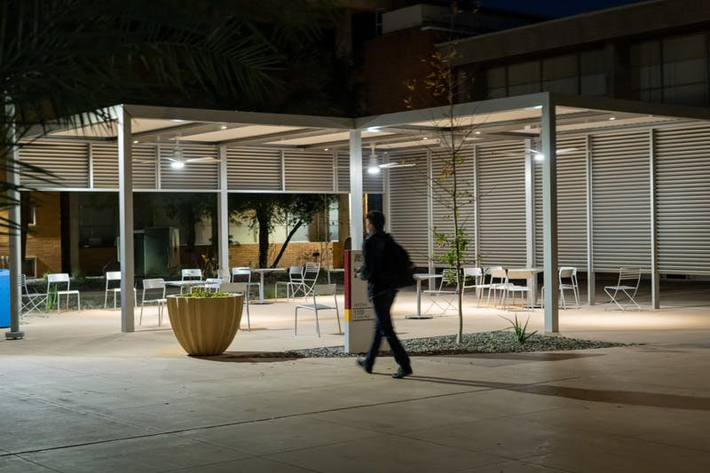 A student walks by the outdoor learning space in front of the Interdisciplinary A building.