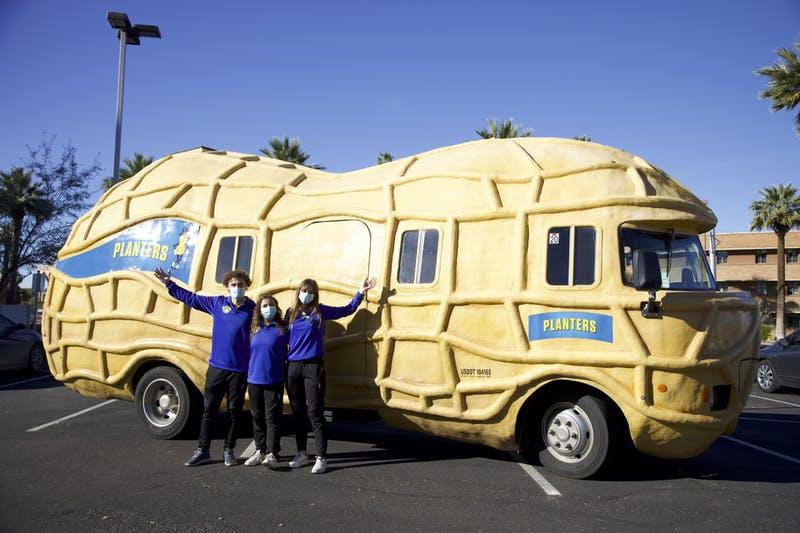 A bunch of people in front of a car shaped like a peanut.