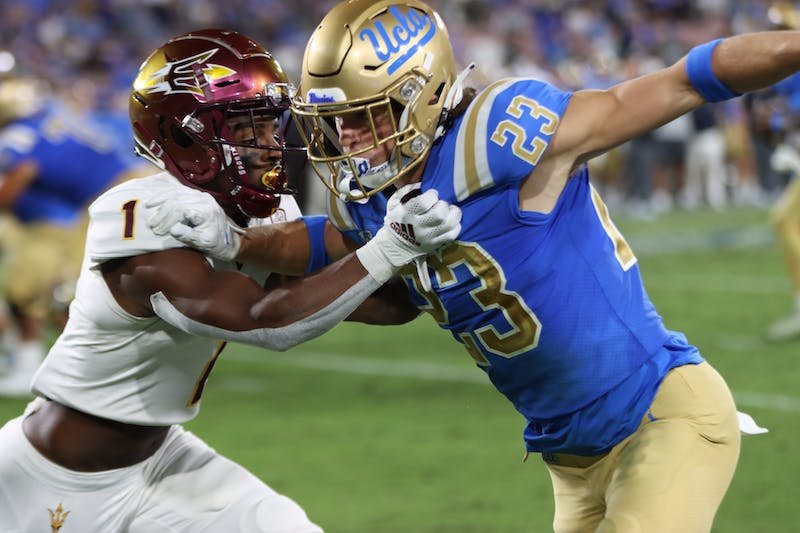 ASU player reaches arms out to cover UCLA wide receiver in Pasadena, California.