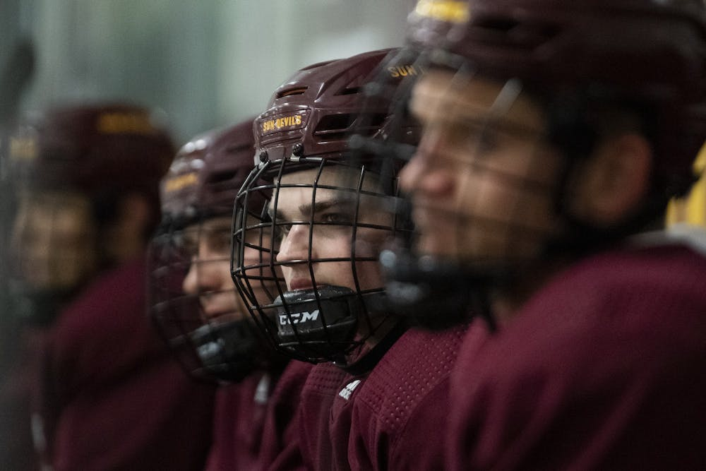 Jack Judson (22) sits on the bench during ice hockey practice