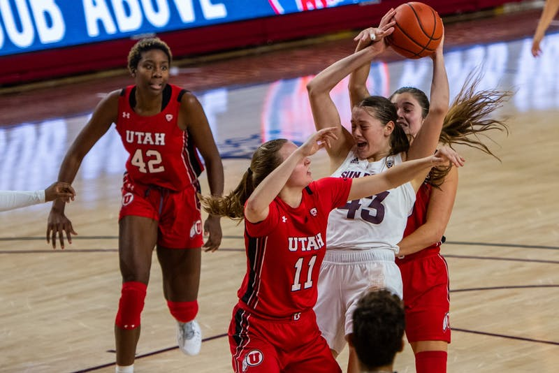 ASU freshman center Imogen Greenslade (43) raises the ball above her head while defending against players from Utah.