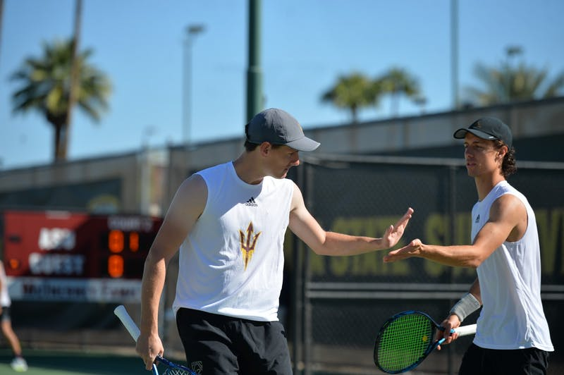 Tim Ruehl congratulates senior Andrea Bolla after scoring a point in a tennis game.