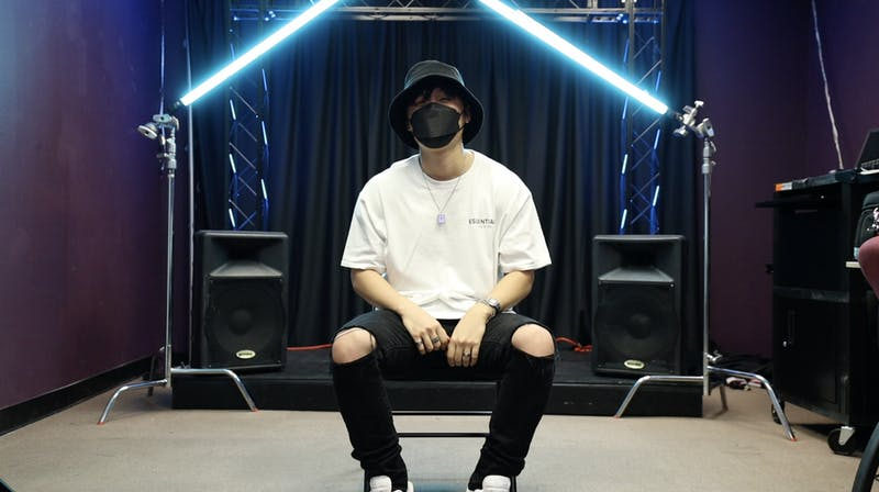 Daniel Oh sitting on a chair surrounded by music video lighting and a studio.
