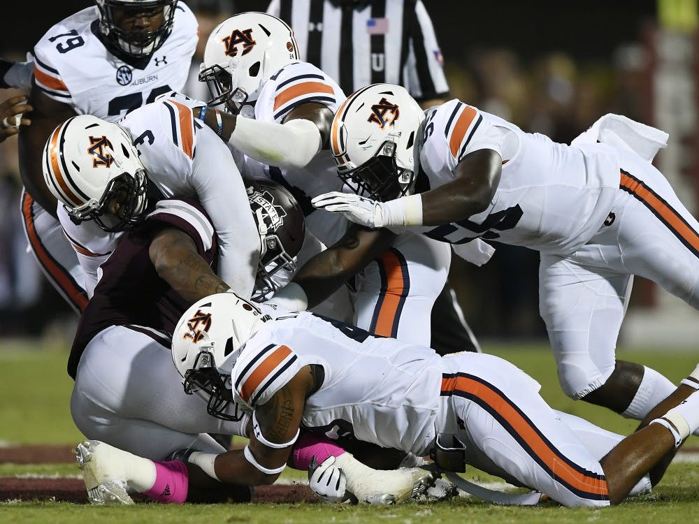 Auburn defenders Montravious Atkinson and Marlon Davidson tackle State's Kylin Hill in the first half.Auburn at Miss State football on Saturday, Oct. 6, 2018 in Starkville, MsTodd Van Emst/AU Athletics