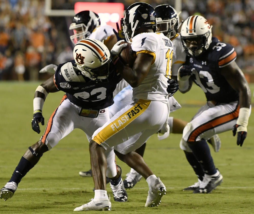 Auburn defenders Roger McCreary and K.J. Britt tackle Mike Carrigan for a short gain in the second half. Auburn Football homecoming vs Kent State on Saturday, Sept. 14, 2019 in Auburn, Ala.