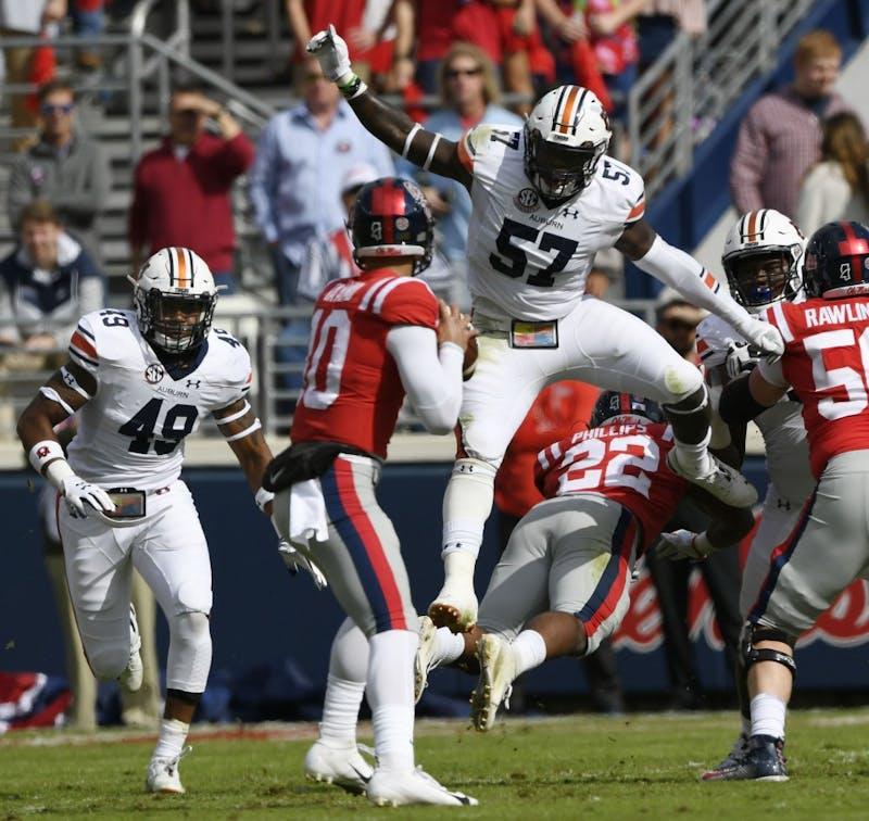 Auburn's Deshaun Davis jumps a blocker to pressure quarterback Jordan Ta'amu in the first half.Auburn at Ole Miss on Saturday, Oct. 20, 2018 in Oxford, MS.Todd Van Emst/AU Athletics