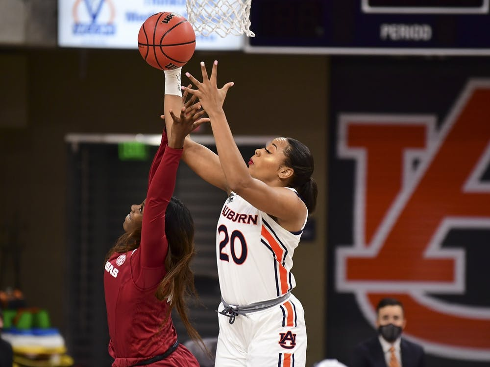 Feb 25, 2021; Auburn, AL, USA; Auburn Tigers forward Unique Thompson (20) grands a rebound ahead of Arkansas Razorbacks forward Erynn Barnum (4) during the game between Auburn and Arkansas at Auburn Arena. Mandatory Credit: Shanna Lockwood/AU Athletics
