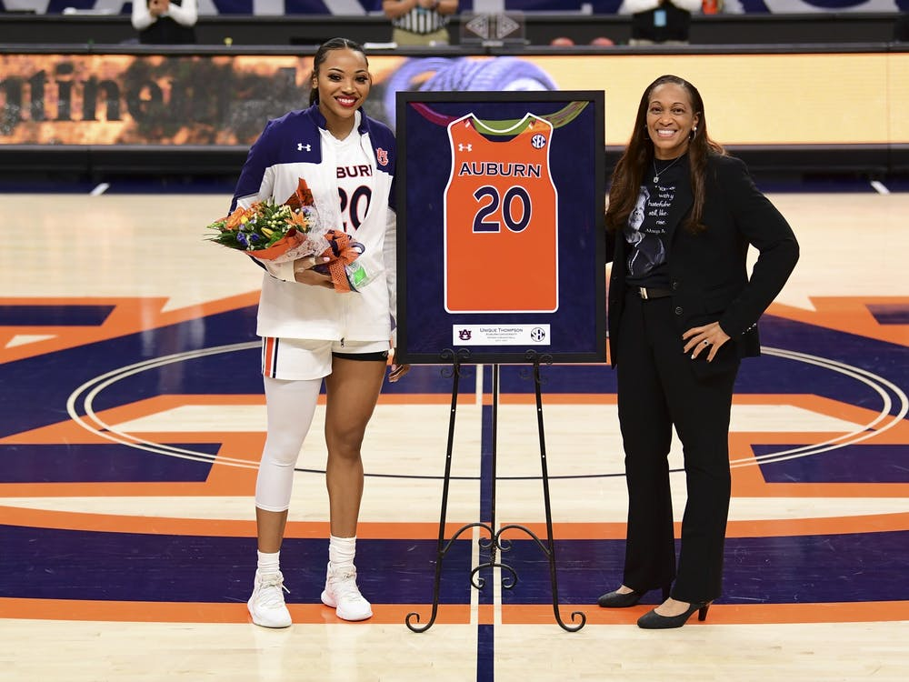Feb 25, 2021; Auburn, AL, USA; Auburn Tigers forward Unique Thompson (20) is presented with a jersey by coach Terri Williams-Flournoy for senior day during the game between Auburn and Arkansas at Auburn Arena. Mandatory Credit: Shanna Lockwood/AU Athletics
