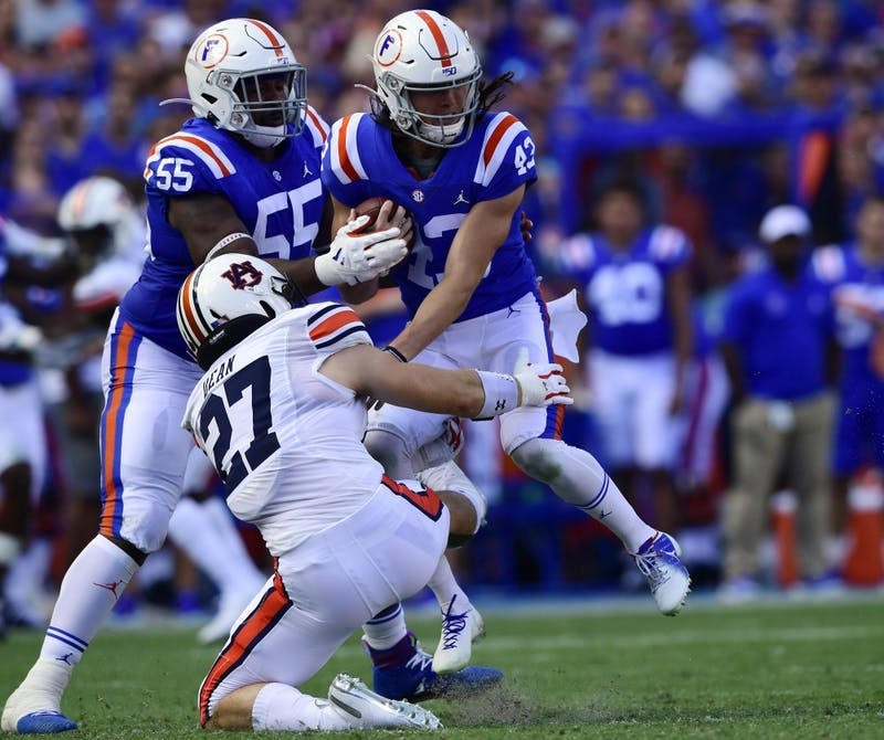 Tanner Dean (27) tackles Florida punter Tommy Townsend running a fake punt in the first half.