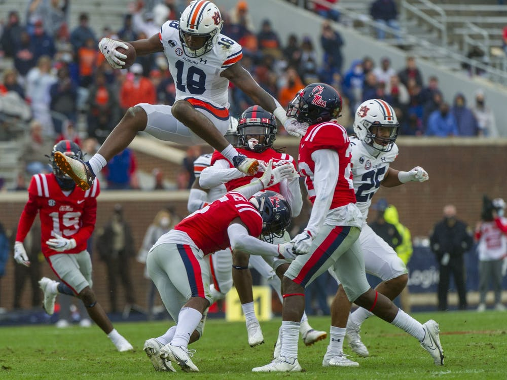 Oct 24, 2020; Oxford, Mississippi, USA;  Auburn Tigers wide receiver Seth Williams (18) leaps over Mississippi Rebels defensive back Jon Haynes (5) during the first half at Vaught-Hemingway Stadium. Mandatory Credit: Justin Ford-USA TODAY Sports