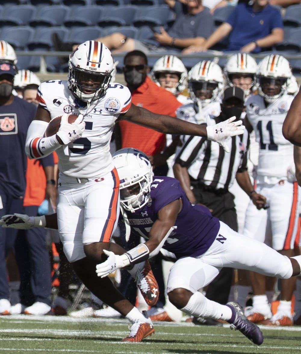 Auburn Tigers wide receiver Kobe Hudson (5) runs through a tackle during the first half of the NCAA Citrus Bowl football game in Orlando, Fla., Friday, Jan. 1, 2021. (Orlando Sentinel Photo/Willie J. Allen Jr.)