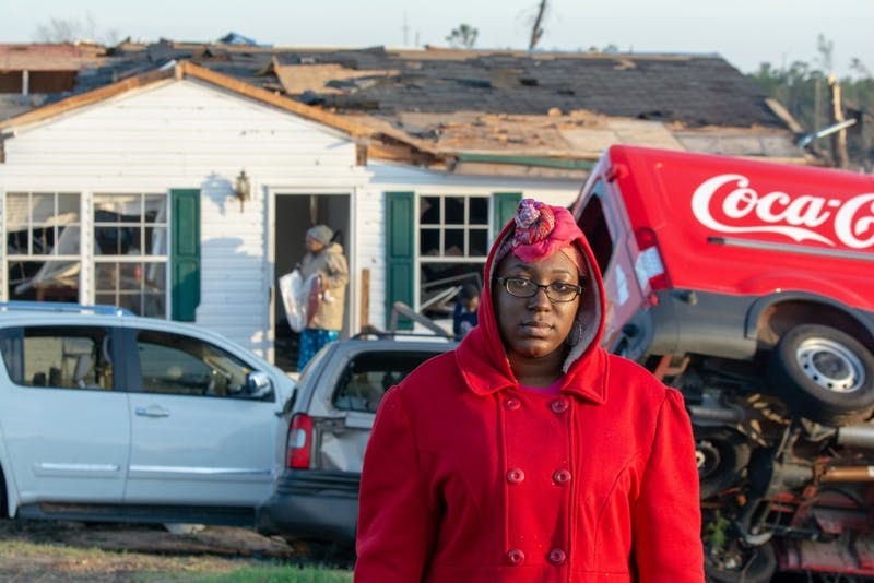Kiara Slater stands in front of her childhood home, where her mom, two brothers and sister survived the storm. Her dad's Coca-Cola delivery truck sits lopsided on the ground in front of the home on March 4, 2019.