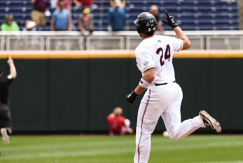 Conor Davis (24) celebrates his ninth-inning home run during Auburn baseball vs. Louisville on June 19, 2019, in Omaha, Neb.