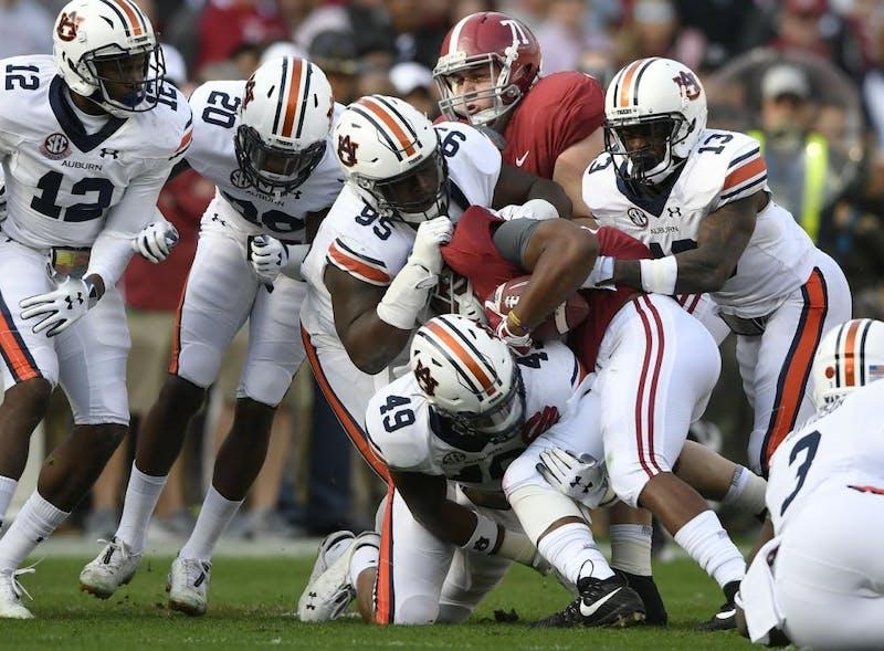 Auburn's defense tackles Alabama's Damien Harris in the first half. Auburn at Alabama football, Iron Bowl, on Saturday, Nov 24, 2018 in Auburn, Ala.
