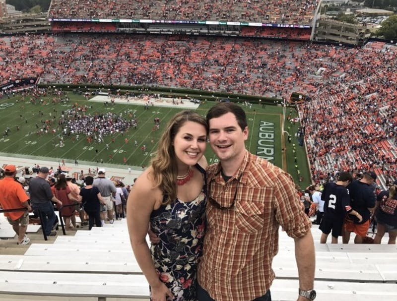Sophie Roth and Frank Pierce pose at a football game in Jordan-Hare Stadium.