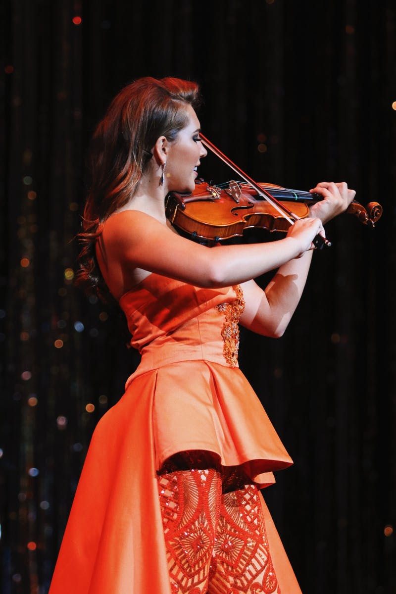 Bradford plays violin during the talent portion of a pageant.
