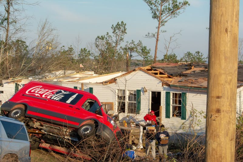 A Coca-Cola truck sits lopsided near a home severely damaged by a tornado that struck southern Lee County on Sunday, March 3, 2019. Crews work to clean up debris from homes destroyed on March 4, 2019.