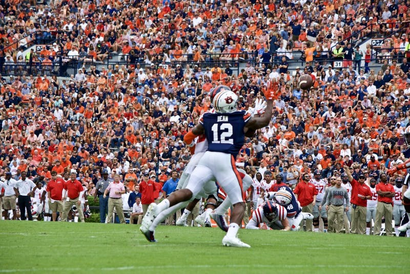 Jamel Dean (12)reaches to swat the ballout of the air. Auburn vs Ole Miss on Saturday, Oct. 7 in Auburn, Ala.