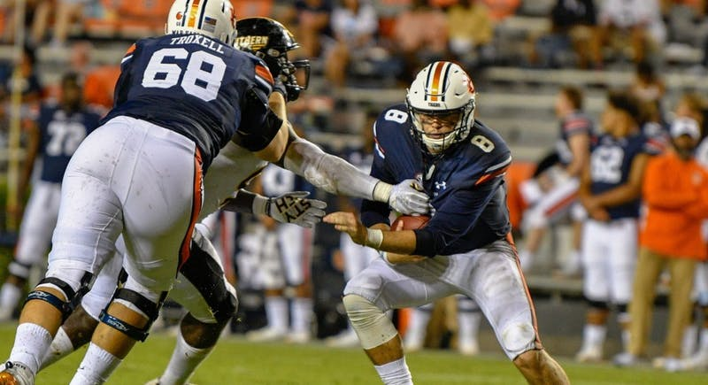 Jarrett Stidham (8) is sacked behind Austin Troxell (68) during Auburn football vs. Southern Miss on Sept. 29, 2018, in Auburn, Ala.