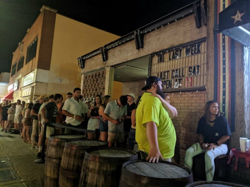 Bar patrons line up outside Quixotes in Auburn, Ala. on Saturday, Aug. 24, 2019.