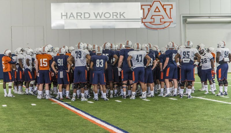 The Auburn football team takes in a few words from head coach Gus Malzahn during practice at the Auburn Athletic Facility, Tuesday, March 29, 2016.