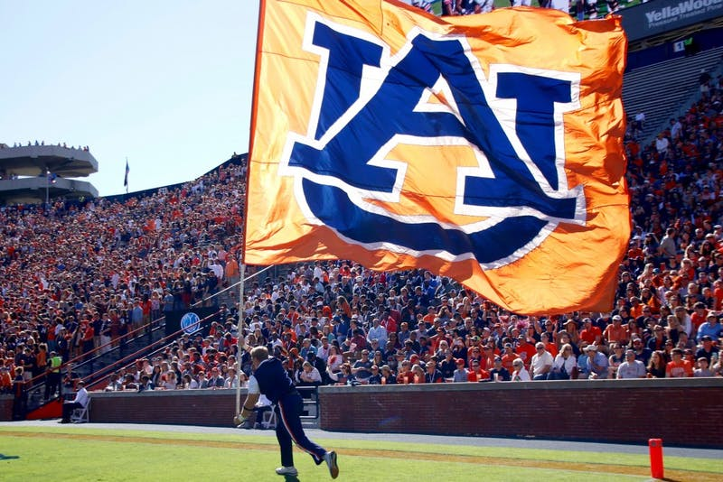 Auburn cheerleader Jackson Walraven runs with the flag during Auburn vs Vanderbilt football game in Jordan-Hare stadium Nov. 5, 2016.