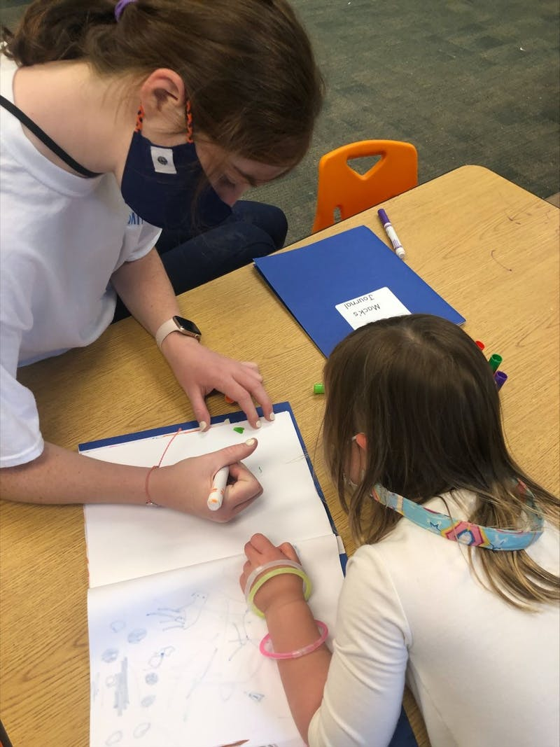 EAGLES Program member engages in a creative activity with a younger kid.
