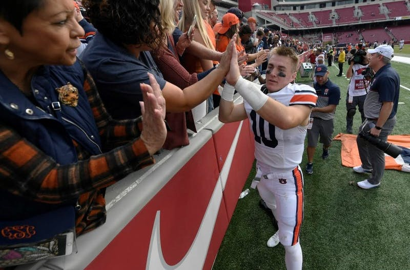Bo Nix (10) high-fives fans after Auburn at Arkansas on Oct. 19, 2019, in Fayetteville, Ark.