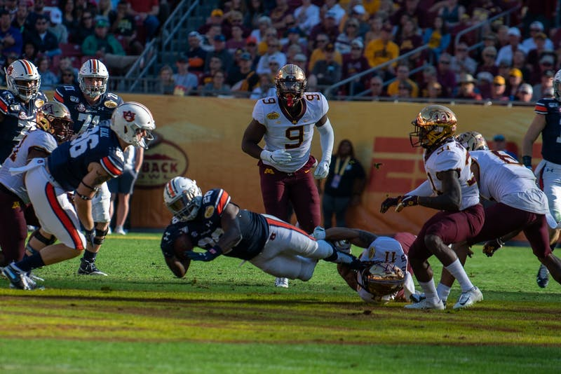 Jatarvious Whitlow (28) gets tackled by a Minnesota defender during Auburn Football vs Minnesota, on Wed, Jan. 1, 2020, in Tampa, Fla.