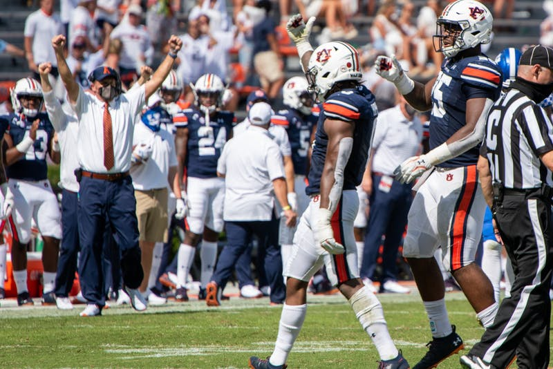 Owen Pappoe (0) celebrates a play, as Gus Malzahn cheers on the sideline during Auburn Football vs. Kentucky on Saturday, Sept. 26, 2020, in Auburn, Ala.