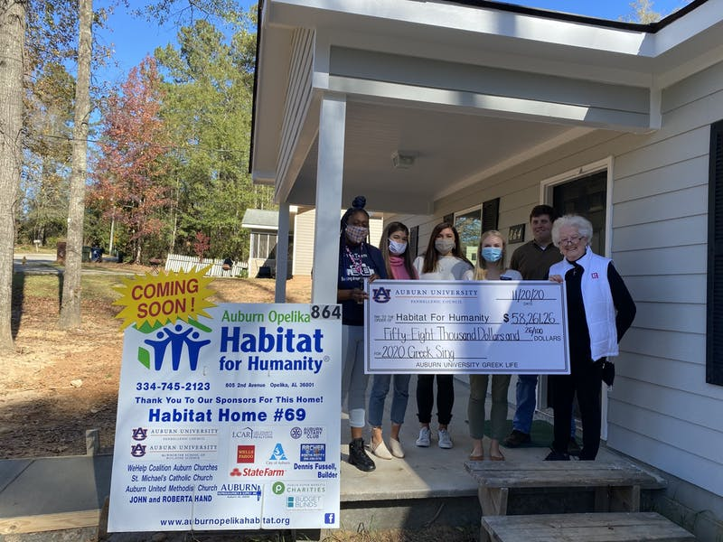 Participants of 2020 Greek Sing display their check for Habitat for Humanity at a sponsored home.