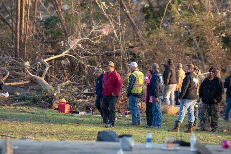 Residents and first responders stand together on March 4, 2019, alongside the wreckage of a home completely destroyed by a tornado that killed 23 people in Beauregard, Alabama, the previous day.