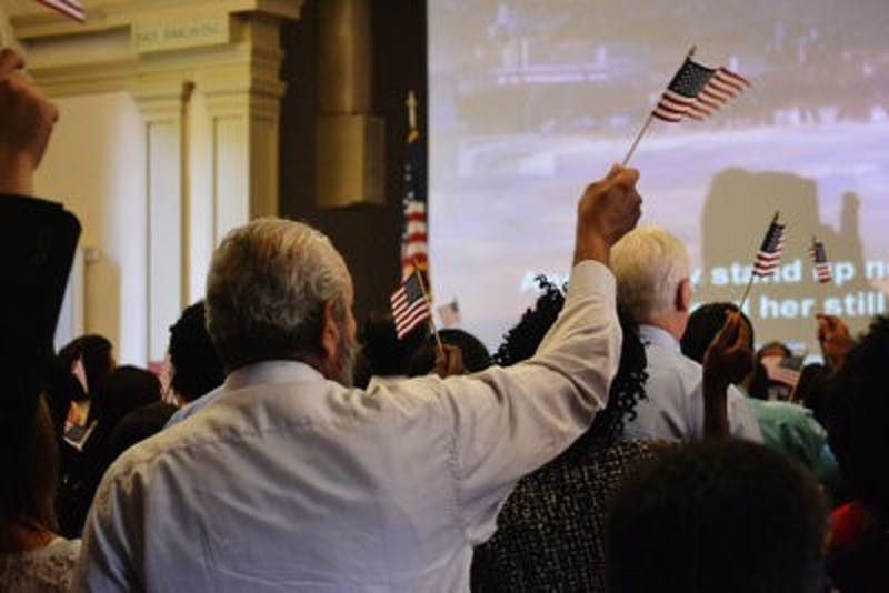 """After watching a short message from President Barack Obama, """"God Bless the U.S.A"""" was played and friends and family sang along with the new citizens. (Danielle Lowe / PHOTO EDITOR)"""