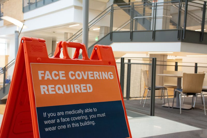 Signs like this remind students, faculty and staff that face masks and social distancing are required in certain parts of the campus.
