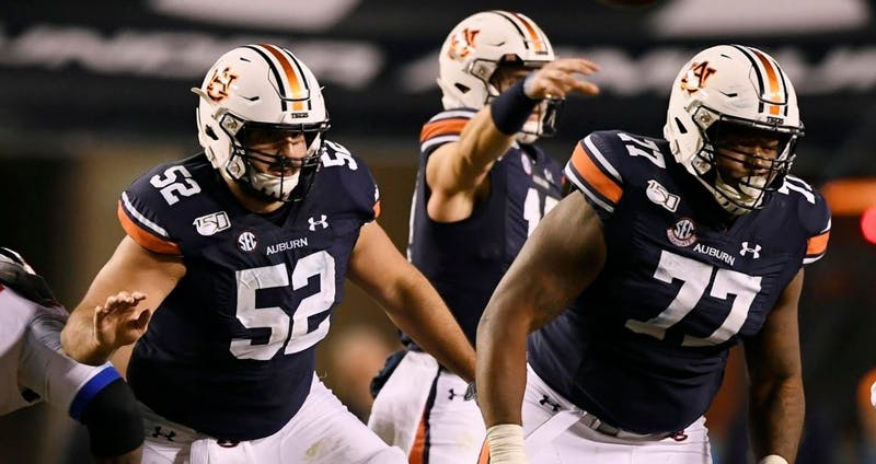 Nick Brahms (52) and Marquel Harrell (77) block for Bo Nix during Auburn vs. Ole Miss on Nov. 2, 2019, in Auburn, Ala.