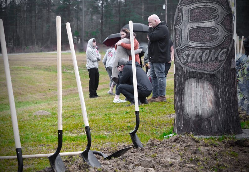 Families comfort one another at the ground breaking of a memorial in Beauregard to honor the lives lost in the tornado that swept through Lee County on March 3, 2019.