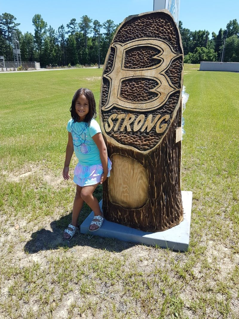 Mattie Ashworth, 7, stands in front of a Beauregard Strong sign.