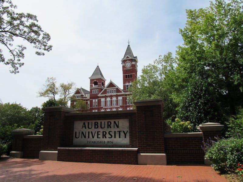 Samford Hall perched behind the Auburn University sign in Auburn, Ala.