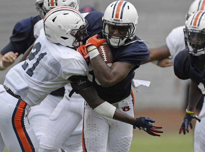 Asa Martin is tackled by Smoke Monday during scrimmage Thursday.